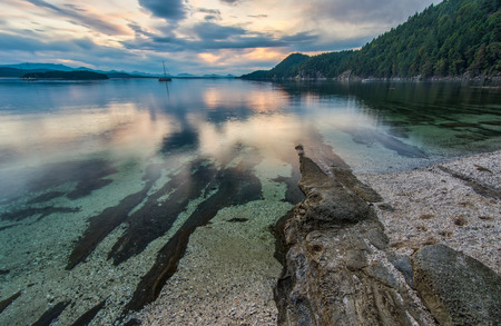 british columbia: Clear water along coast with a boat