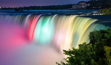 the edge of horseshoe falls: Niagara falls lit by colorful lights of many colors