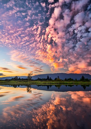 dramatic clouds: Reflection of dramatic pink clouds in water