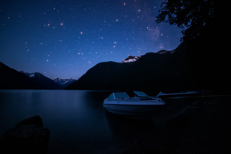 Milky way over lake and boats