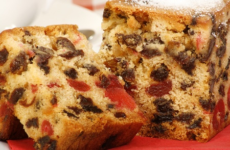 fruitcake: delicious sliced fruit cake with mixed fruit and cherries on a red napkin Stock Photo