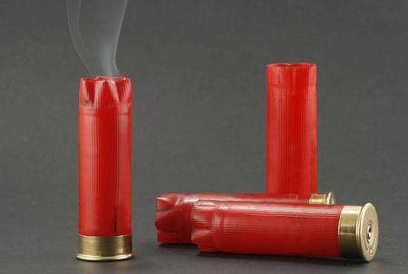 회색 배경에 흡연 샷건 카트리지 스톡 콘텐츠