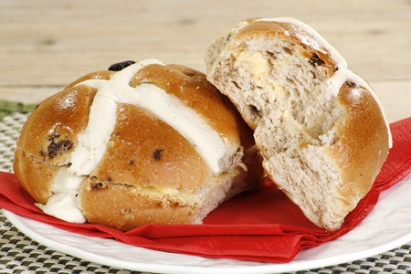 british food: two buttered hot cross buns on a white plate
