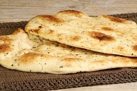 two pieces of garlic and coriander naan on a wooden table photo