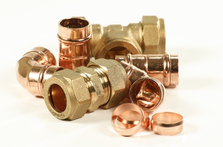 copper: selection of plumbers pipe fittings isolated on a white background