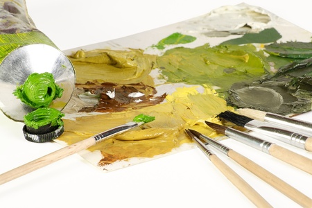 artists brushes pallette and oil paint on a white background Stock Photo