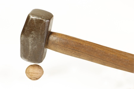 cracking: sledgehammer about to crush a walnut, excess force concept