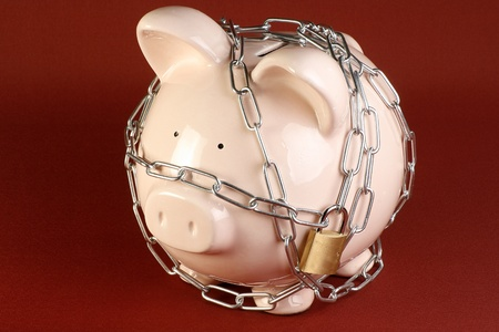 thrift box: security concept pink piggy bank wrapped in chains and padlocked