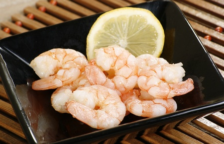 cooked king prawns and lemon in a black dish Standard-Bild