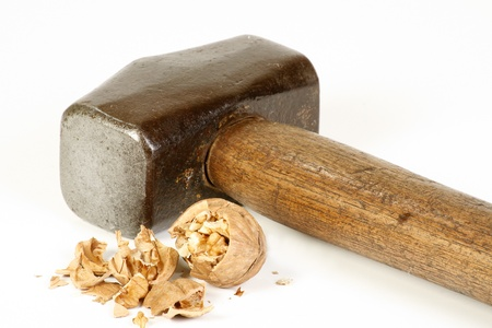 cracking: old sledge hammer and crushed walnut on a white background, excess force concept Stock Photo