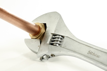 metal pipe: adjustable spanner and pipe fitting isolated on a white background Stock Photo