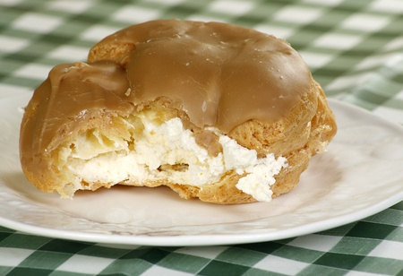 choux bun: delicious choux bun with toffee icing filled with fresh whipped cream Stock Photo