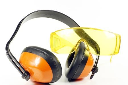 elementos de protección personal: los defensores de los naranjos del oído y anteojos de seguridad, aislado en un fondo blanco Foto de archivo