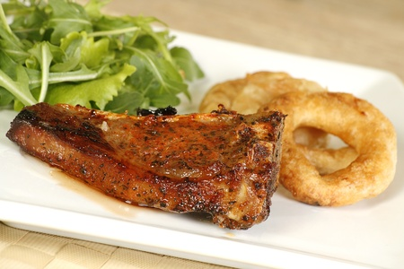 rocket lettuce: grilled lamb cutlet with onion rings and rocket lettuce