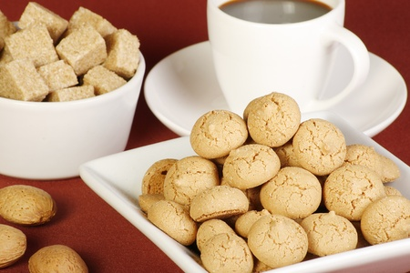 amaretto: dish of amaretto biscuits coffee sugar and almonds on a red tablecloth Stock Photo