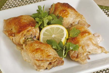 thighs: four roast chicken thighs with coriander and lemon on a white plate Stock Photo