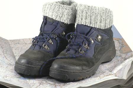 pair of hiking boots resting on a map photo