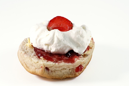 scone: scone with strawberry jam and cream isolated on white