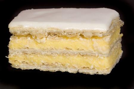 custard slices: single iced custard slice cake on a black background Stock Photo
