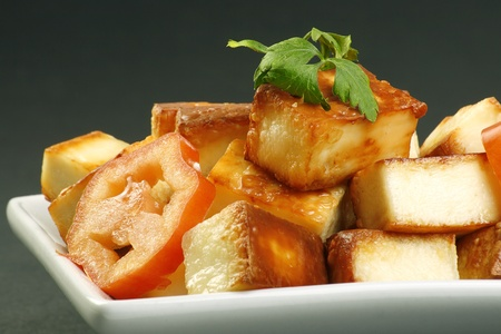 cooked indian paneer cheese and tomato on a grey background