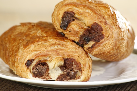 french roll: close up of two pain au chocolat on a white plate