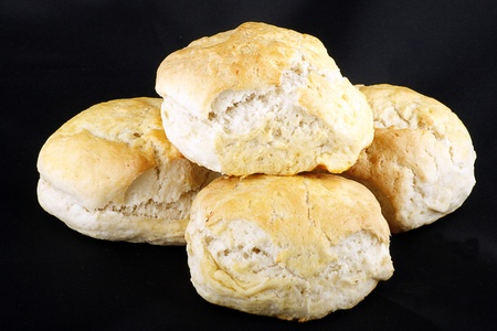 scone: four fresh baked scones isolated on a black background