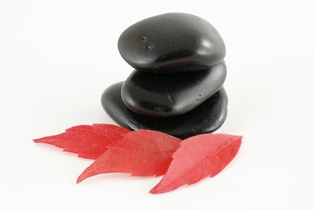 three stacked black stones isolated on a white background photo