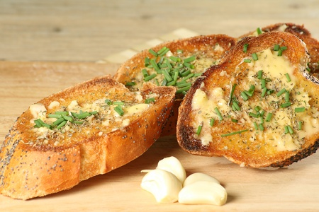 crusty french bread: slices of toasted garlic bread with chopped chives on a wooden board Stock Photo