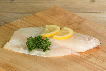cod fillet uncooked on a wooden board