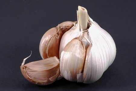 split garlic bulb isolated on a black background photo