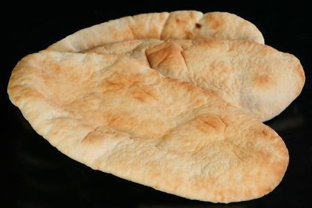 pita bread: three portions of pitta bread on a black background Stock Photo