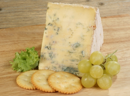 british food: Derbyshire blue stilton cheese with grapes and cheese crackers on a wooden board Stock Photo