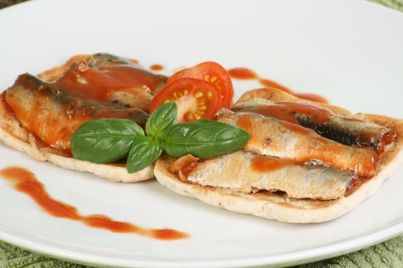 sardinas: sardinas y salsa de tomate con tomate y albahaca sobre una tostada de pan plano Foto de archivo
