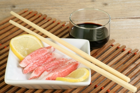 surimi on a white dish with lemon slices and soy sauce
