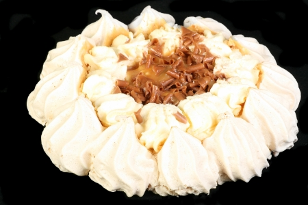 whole toffee pavlova isolated on a black background photo