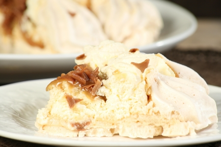 portion of toffee topped pavlova with cream and toffee curls