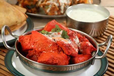 Asian chicken tikka pieces with mint sauce and mint garnish Standard-Bild
