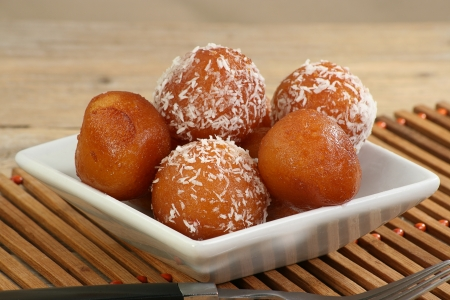 spongy: asian gulab jamun on a white dish with coconut