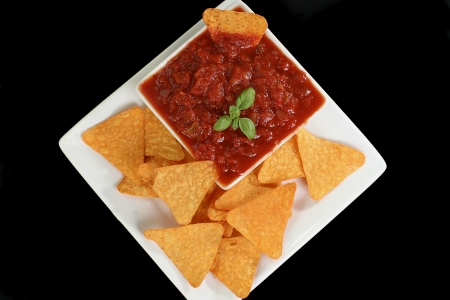 corn chip: tortilla chips and salsa sauce isolated on a black background