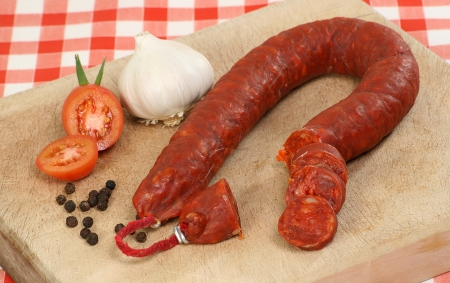 chorizos: sliced chorizo tomato and garlic on a wooden board