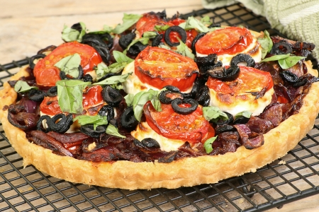 caramalised onion and goats cheese tart with tomato and olives Standard-Bild
