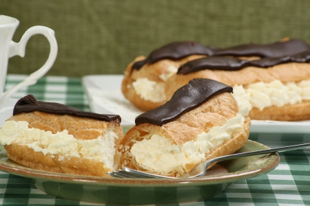 delicious cream filled chocolate eclairs on a green table cloth