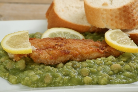 uk cuisine: fillet of fried fish on a bed of mushy peas