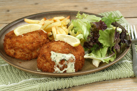 uk cuisine: breaded cod fish cakes with parsley sauce salad and fries                                Stock Photo