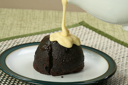 dark chocolate sponge dessert with pouring custard