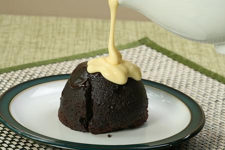 dark chocolate sponge dessert with pouring custard Reklamní fotografie