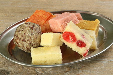 gulab:   selection of delicious indian sweets on a metal dish