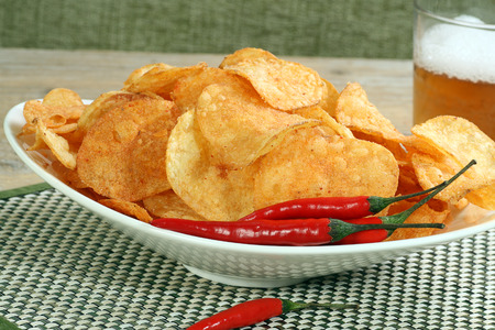 flavoured:  sour cream and chilli flavoured potato chips or crisps on a white plate
