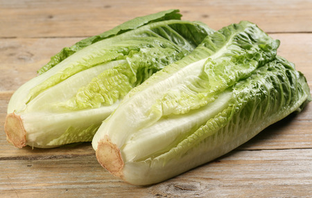two hearts of romaine lettuce on a rustic wooden board