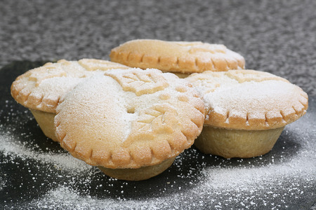carne picada: cuatro mince pies navidad espolvoreadas con azúcar glas Foto de archivo